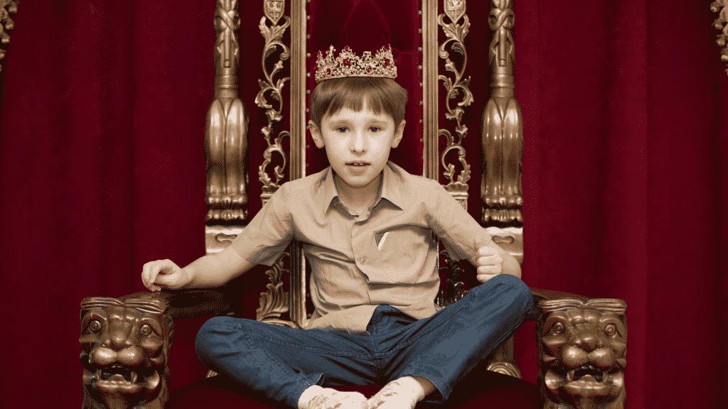 Garoto sentado com as pernas cruzadas em trono usando uma coroa de rei