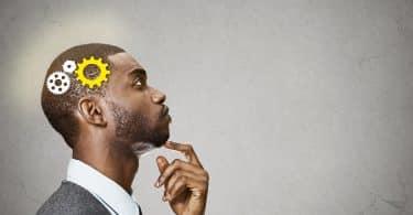 Homem com semblante pensativo. Em sua cabeça, há desenho representativo de engrenagens.