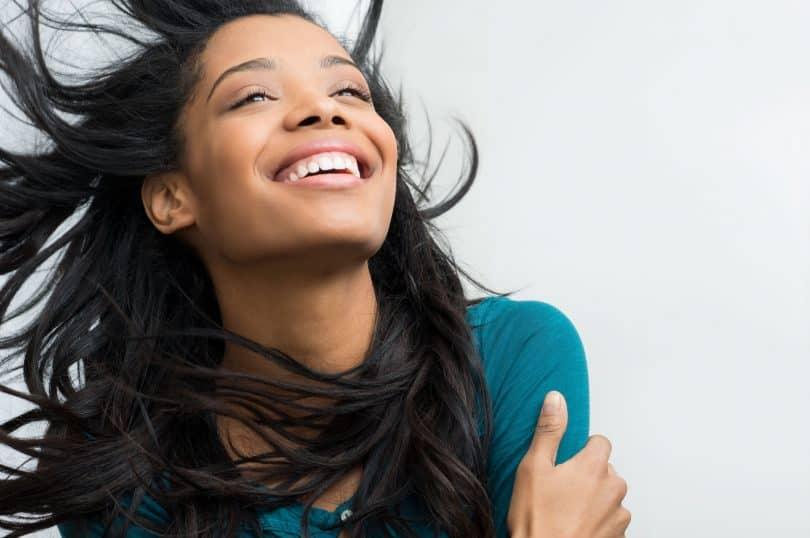 Garota sorri e toca os próprios braços.