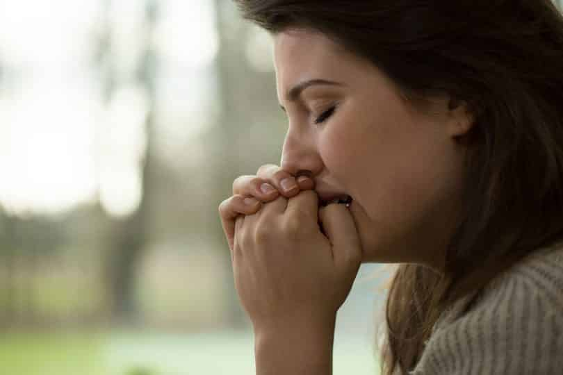 Mulher aflita com as mãos próximas da boca.