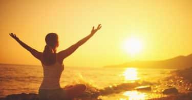 Mulher com os braços erguidos. Ela está sentada em uma pedra a frente do mar. Ao fundo, há o pôr do sol.
