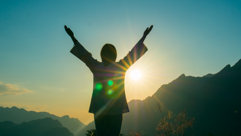 Silhueta de homem com os braços erguidos observando o sol nascer