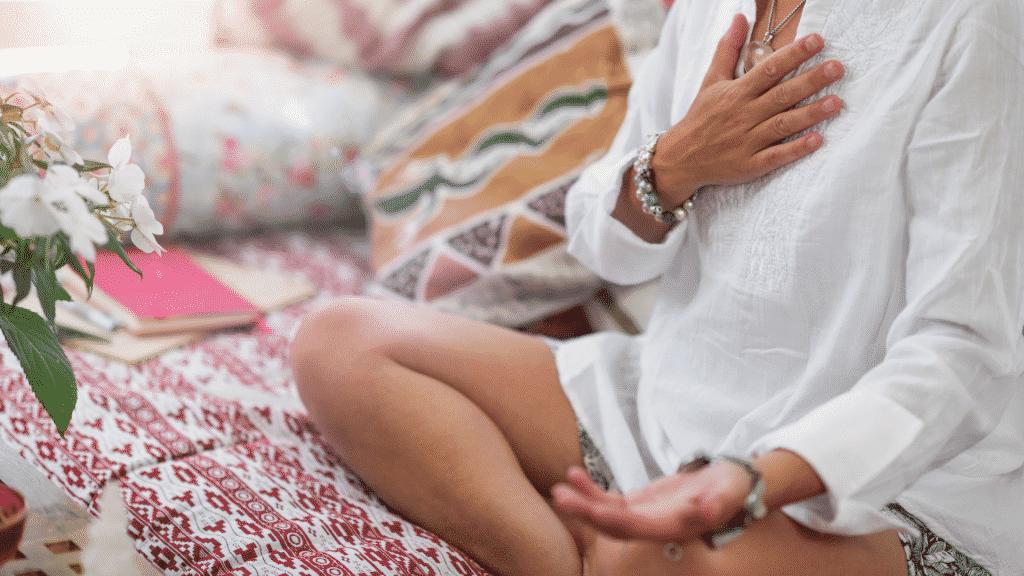 Mulher meditando com a mão no chakra cardíaco