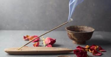 Imagem de fundo cinza e em destaque temos um incensário com um incenso de massala aceso, algumas flores espalhadas sobre a mesa e um pote de ferro.