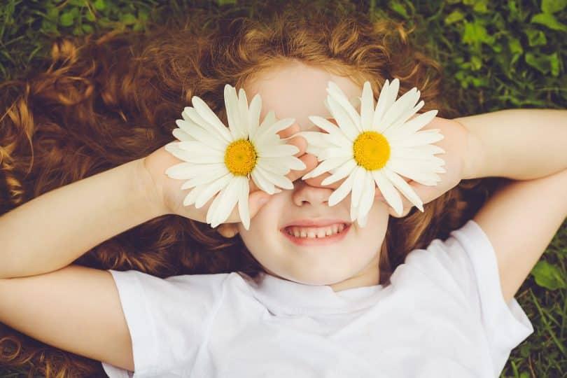 Menina branca segurando flores em seus olhos enquanto sorri.