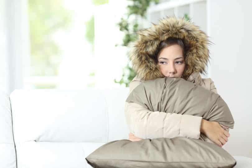 Mulher agasalhada agarra travesseiro.