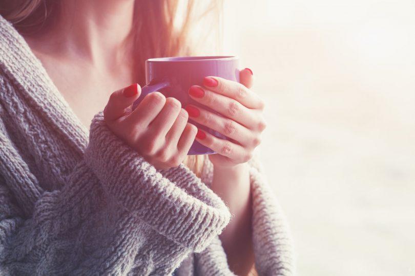 Mãos segurando xícara.