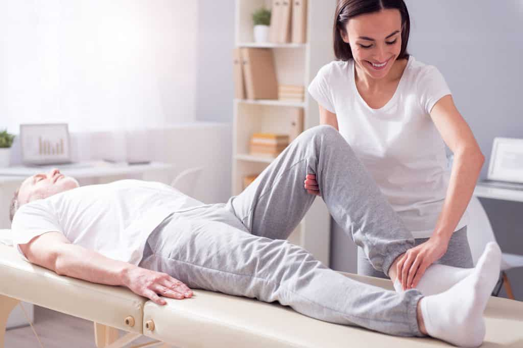 Doutora alongando perna do paciente