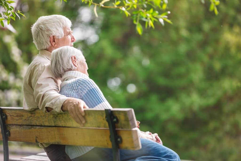 Casal de idosos sentado em um banco em um parque.