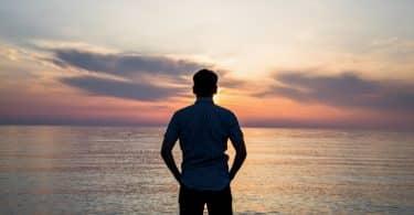 Silhueta de homem olhando para o pôr do sol e o mar.