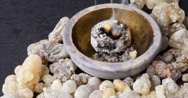Imagem de um incensário e dentro dele um incsenso de sálvia sendo queimado. Ao lado do incensário vários tipos e tamanhos de pedras na cor branca complementam a decoração.