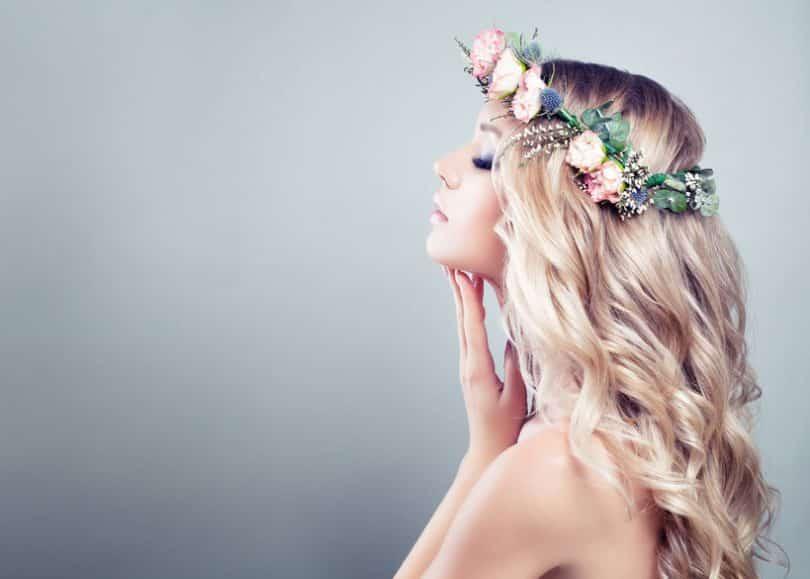 Mulher de olhos fechados toca o queixo. Ela está de perfil e com uma coroa de flores na cabeça.