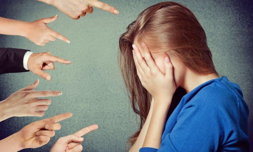 Mãos apontam para mulher que coloca o rosto sob as mãos.