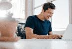 Homem sorrindo em frente ao notebook