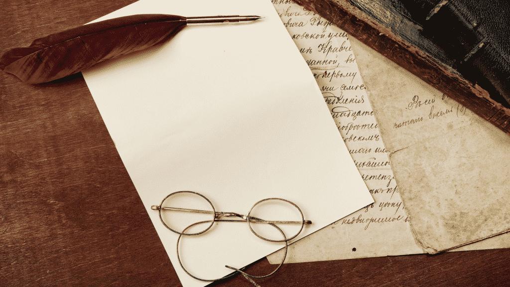 Imagem de folhas em cima de uma mesa, uma caneta de pena e um óculos de grau