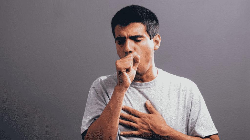 Imagem de um homem tossindo e com a mão no peito