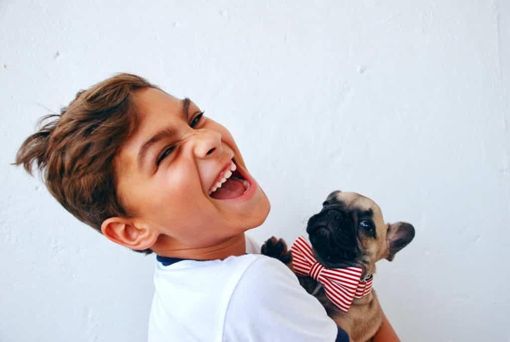 Menino branco sorrindo com cachorro no colo.