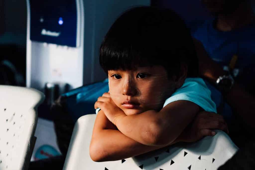Criança oriental com expressão triste.