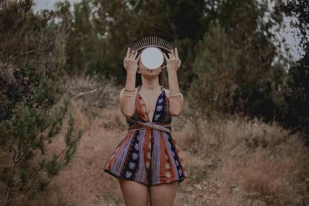 Mulher branca num bosque segurando espelho no formato de olho.