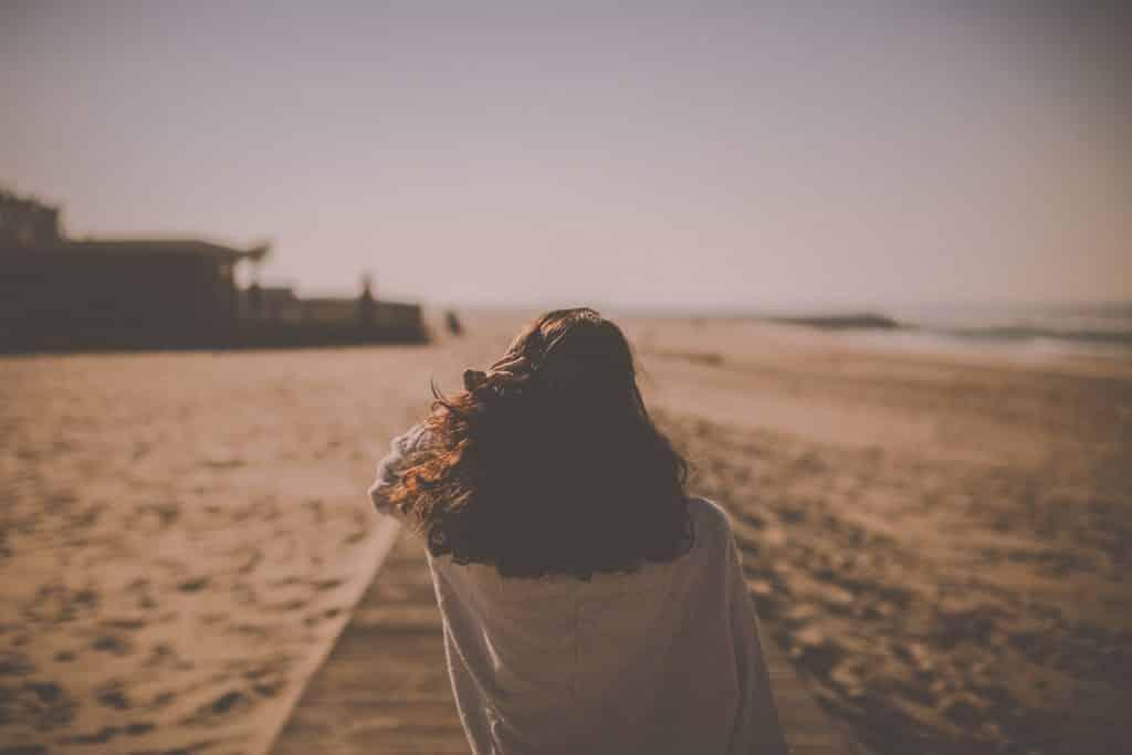 Mulher de costas numa praia.
