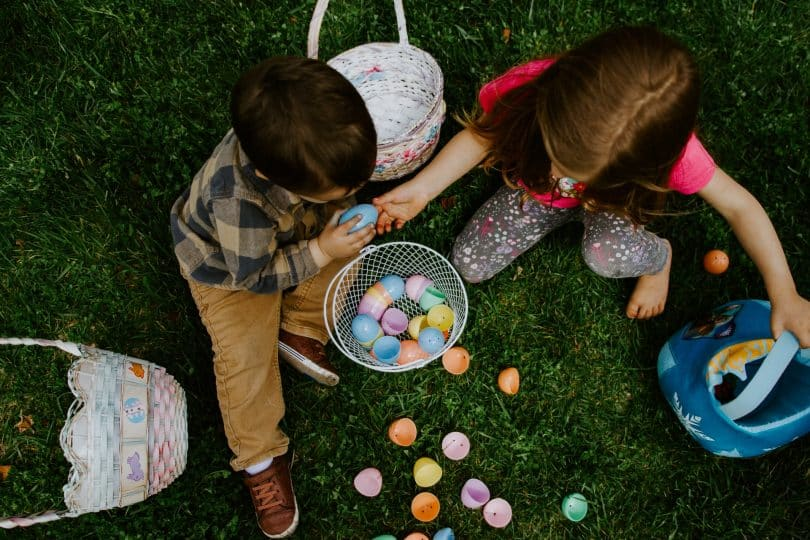 Crianças brancas brincando com ovos coloridos.