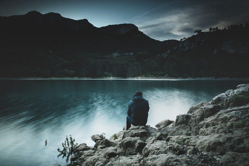 Homem agachado em rochas na beira de um rio.