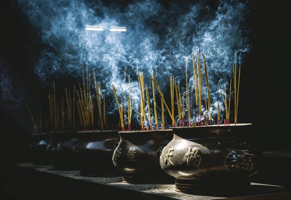 Imagem de várias panelas de ferro representando um incensário e dentro delas vários incensos de lavanda sendo queimados. No ambiente tem muita fumaça.