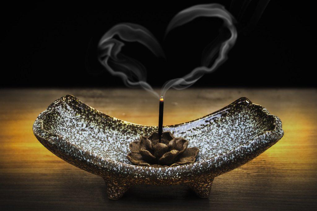 Imagem de um incensário na cor cinza e branco e dentro dele um incenso de lavanda sendo queimado. Do incenso sai uma fumaça que traz o desenho de um coração.