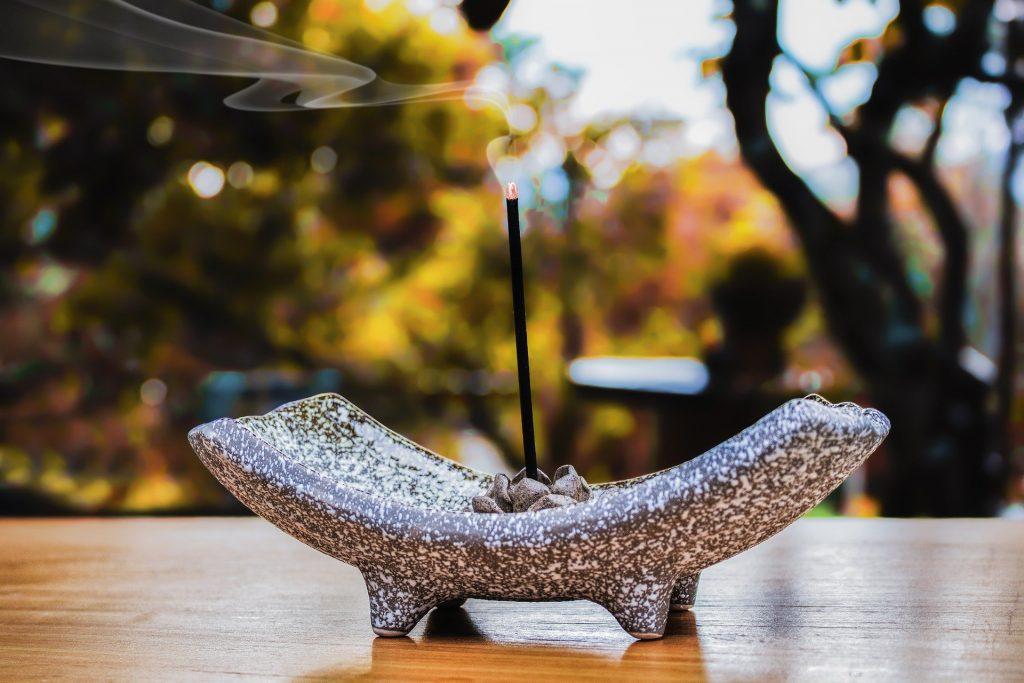 Imagem de um incensário feito de mármore nas cores cinza e branco e dentro dele um incenso de lavanda aceso. Ao fundo da imagem, temos várias árvores.