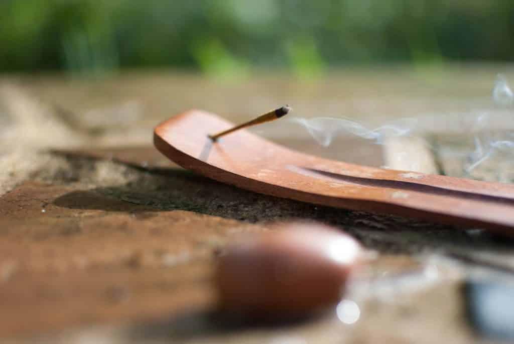 Imagem de um incensário sobre uma mesa de madeira. Nele está sendo queimado um incenso de massala. Ao lado dele, uma pedra pequena na cor marrom.