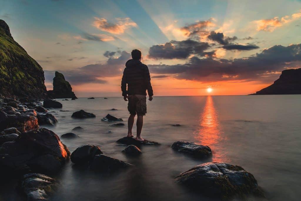 Homem de costas numa praia no pôr-do-sol.