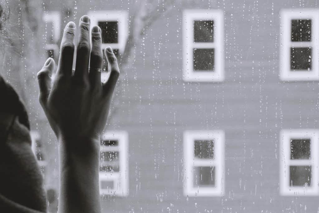 Imagem em preto e branco de uma mão sobre o vidro de uma janela