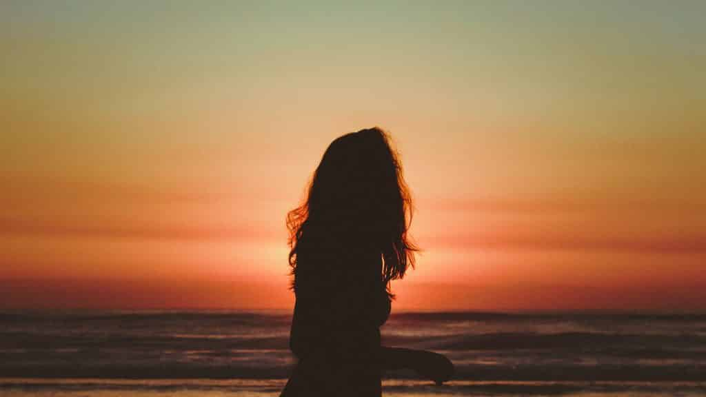 Uma mulher na praia em frente ao pôr sol