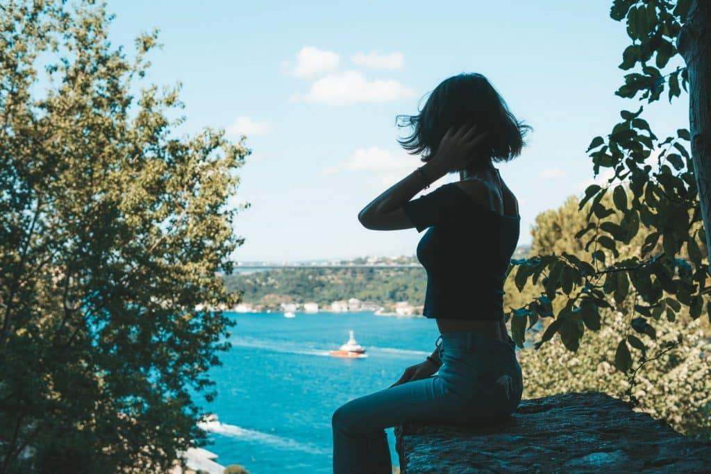 Menina sentada de costas numa pedra.