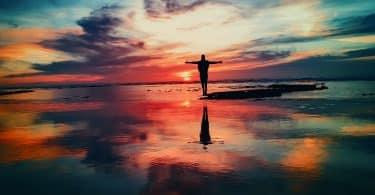 Pessoa de costas na beira do mar durante o pôr-do-sol.