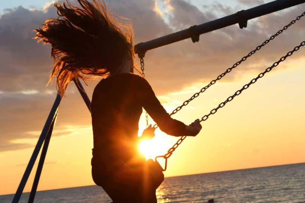 Mulher branca se balançando num balanço na praia.