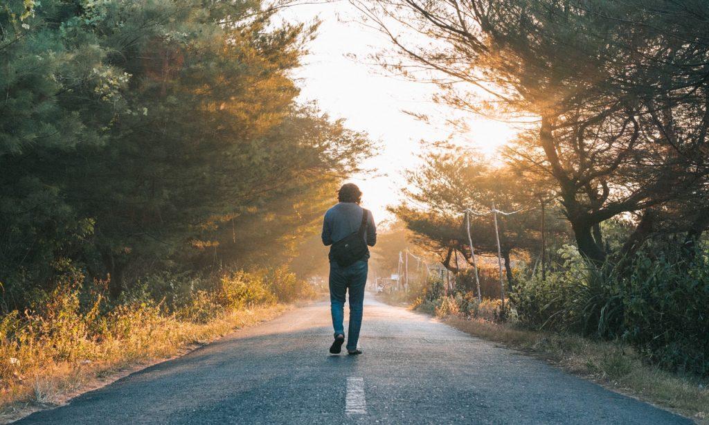 Homem caminha em estrada asfaltada em meio a árvores.