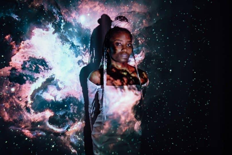 Mulher negra iluminada por imagens de galáxias.