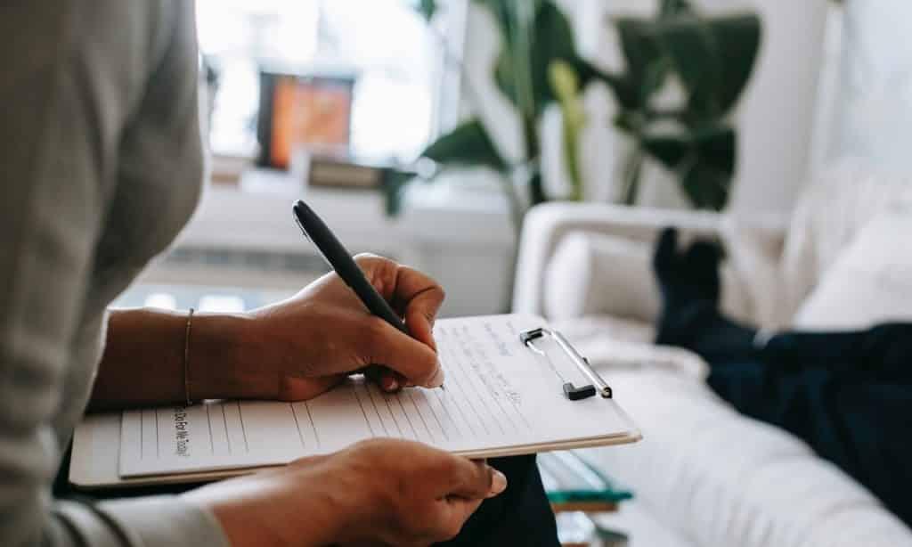 Mulher escreve em folha sobre prancheta. Ao fundo, em segundo plano, há um homem deitado no sofá em sua frente.