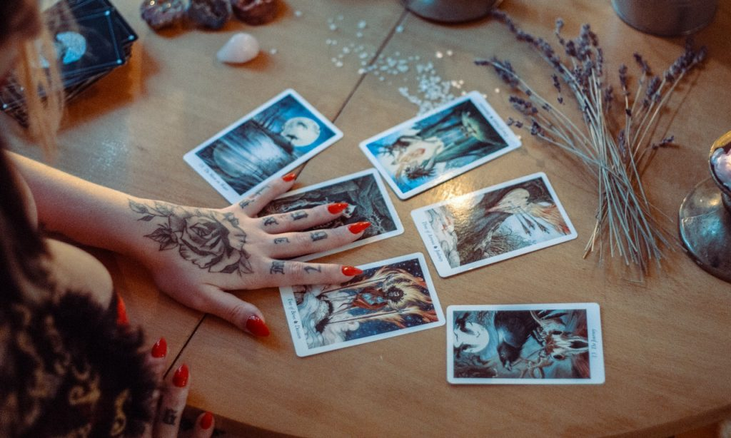 Cartas de tarot postas sobre mesa. Uma mulher as manipula.
