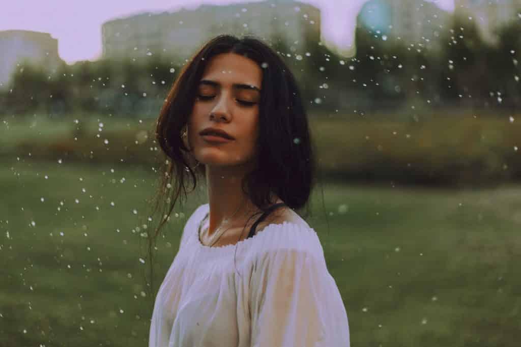 Mulher de olhos fechados em um gramado