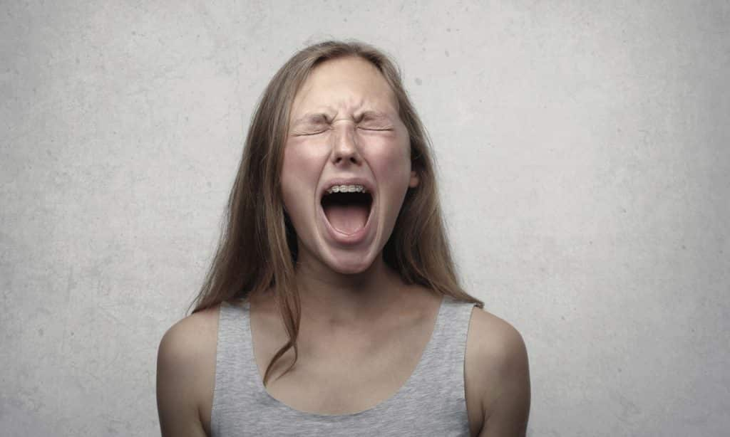 Mulher gritando com olhos fechados.