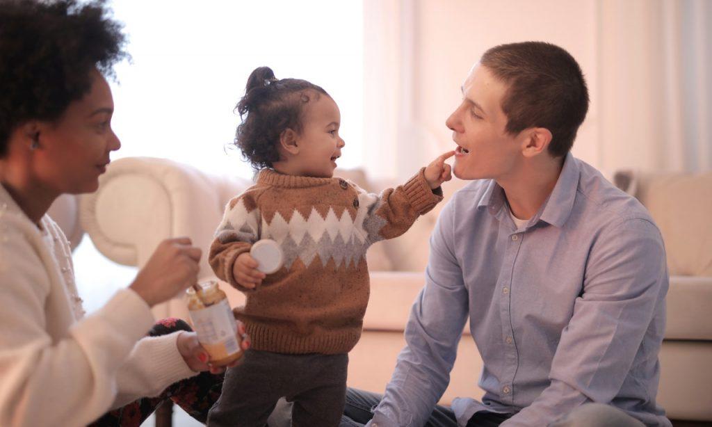 Criança brinca com dois adultos.