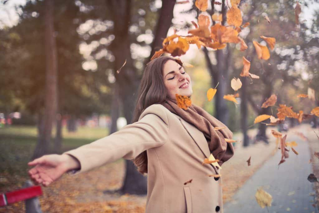 Mulher sorrindo jogando folhas para o alto