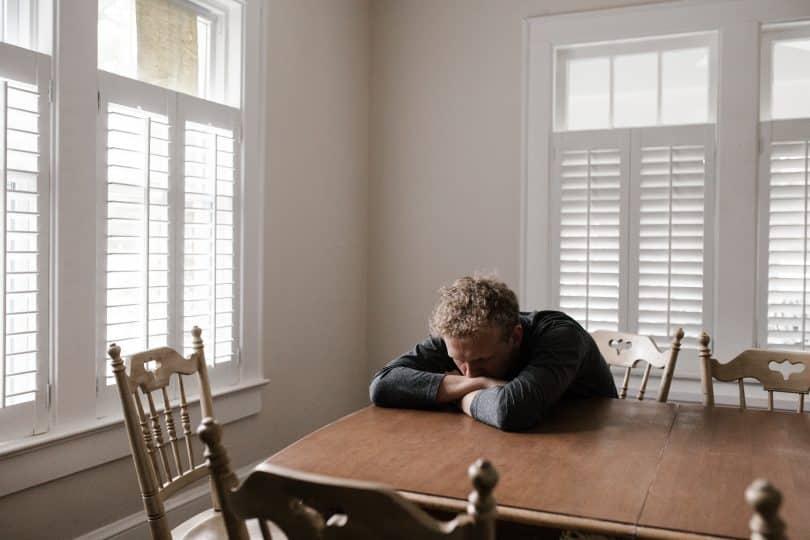 Homem sozinho sentado à mesa com sua cabeça deitada em seus braços