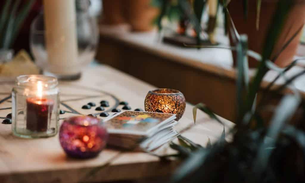 Cartas de tarot postas em pilha sobre mesa. Ao lado, há três diferentes velas.