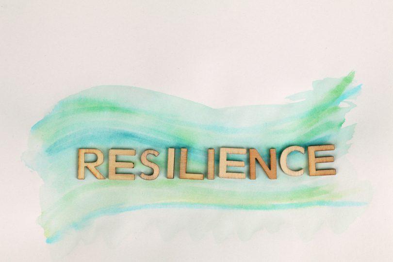 """Palavra """"resilience"""" escrito em dourado."""