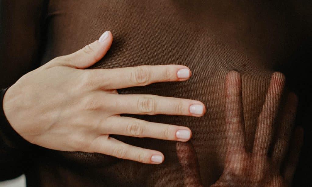 Mulher com as mãos sobre os seios.