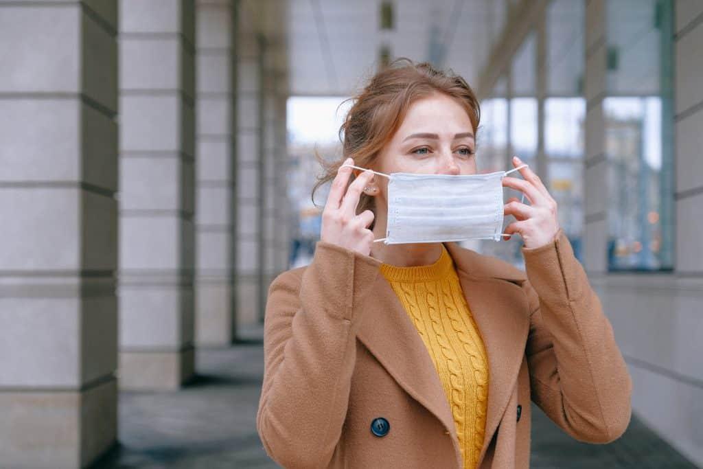 Mulher coloca máscara sobre o rosto