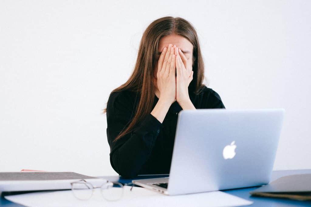 Mulher de frente para o notebook com as mãos em seu rosto